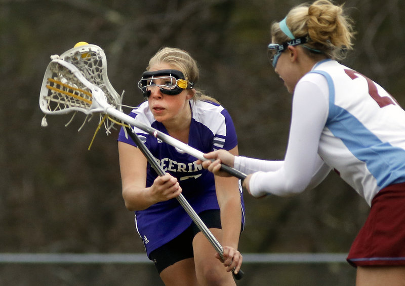 Maddy Mazjanis of Deering keeps her eyes on the ball while trying to keep it away from Lauren Coughlin of Windham. The game was the first of the season for both teams.