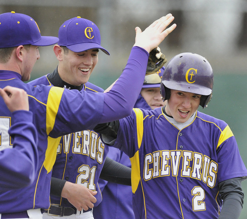 Charlie Mull of Cheverus, right, is welcomed by teammates Tuesday after scoring on a Sanford throwing error. The Stags came away with a five-inning victory against the Spartans, 10-0.