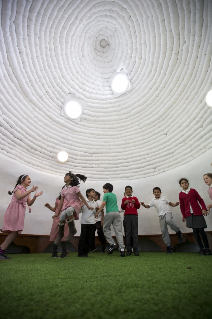 "School pupils ages 6 and 7 play inside ""The Big Adobe,"" built on their playground in London on Thursday."