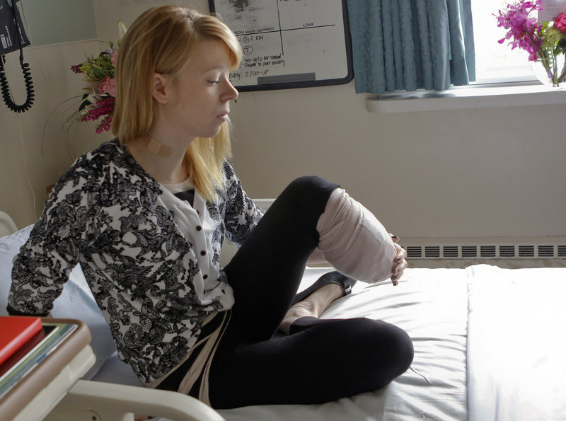 Adrianne Haslet, a professional ballroom dancer injured by a bomb that exploded near the Boston Marathon finish line, lifts her bandaged left leg in her bed Wednesday.