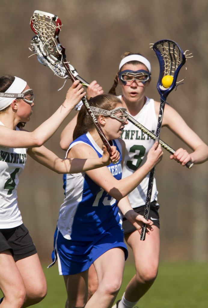 Hayley Fecko of Kennebunk attempts to manuever the ball between defenders Sofia Canning, left, and Heidi Cole of Waynflete during their girls' lacrosse game Saturday. Waynflete pulled away to a 16-1 victory.