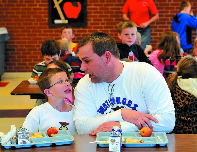 Todd Atwood, a volunteer Watch Dog at Belgrade Central School, sits with his son Luke, 8, during lunch Thursday.