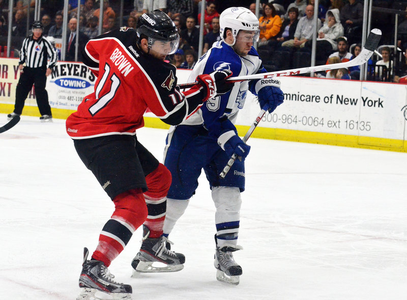 Portland's Chris Brown takes a shot as he jousts with Syracuse's Tyler Johnson during first-period action of Game 2 of the first round of the Calder Cup series in Syracuse, N.Y., won by the Crunch. Down 2-0, the Pirates must win Thursday to avoid elimination.