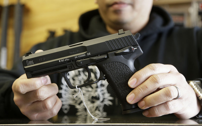 The general manager of a San Francisco gun shop holds an HK USP 9 mm handgun. Addressing