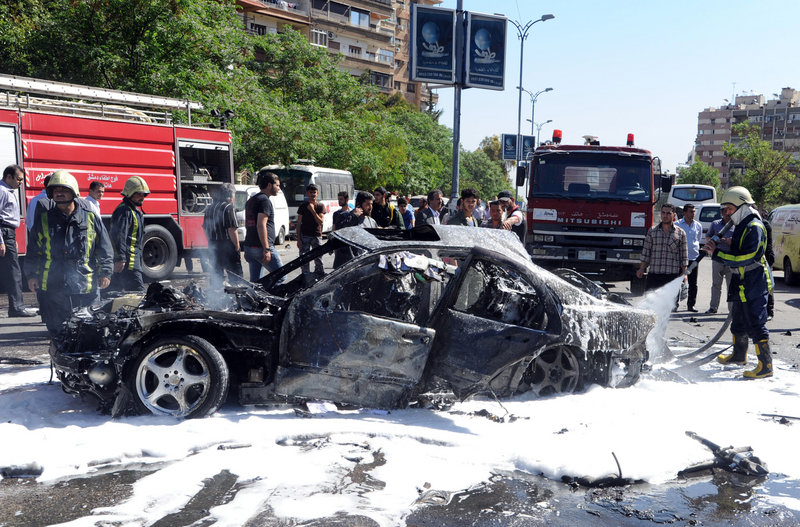 A photo released by the Syrian official news agency SANA shows firefighters extinguishing burning vehicles after a car bomb exploded in the posh capital neighborhood of Mazzeh.