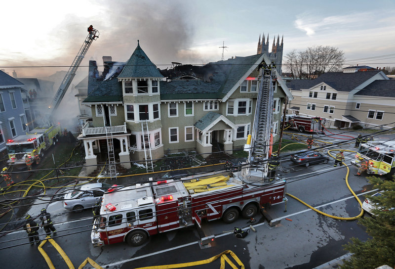 Firefighters battle a fire that began on Blake Street in Lewiston. Hundreds of spectators watched, and several blocks were cordoned off as the flames were fought from ladders and the ground.