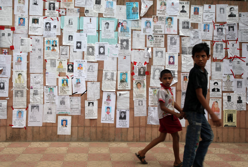 Two boys walk past a wall pasted with fliers showing some of the missing in the Savar, Bangladesh, building collapse. Rescuers on Monday gave up hope of finding more survivors.