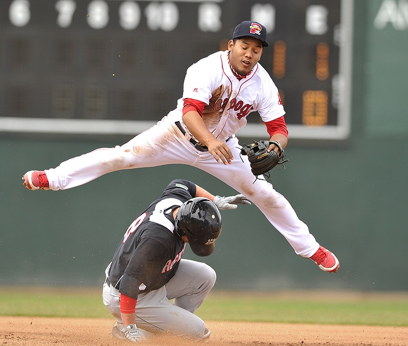 Second baseman Heiker Meneses of the Portland Sea Dogs vaults over Dan Rohlfing of the New Britain Rock Cats, throwing to first to complete a double play Saturday during a 7-1 victory. Portland moved over .500 for the first time this season.