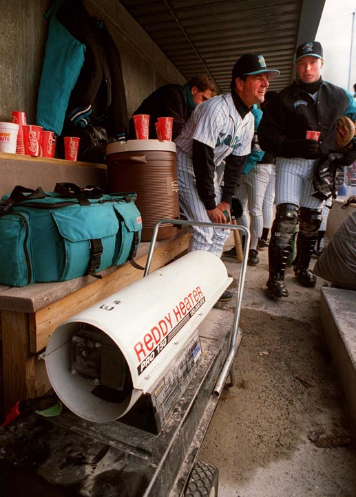 FILE PHOTO BY JOHN EWING --APRIL 6,1995-Portland Sea Dogs manager Carlos Tosca takes advantage of a dugout heater during last season's home opener. Next to him is returning catcher Mike Redmond.