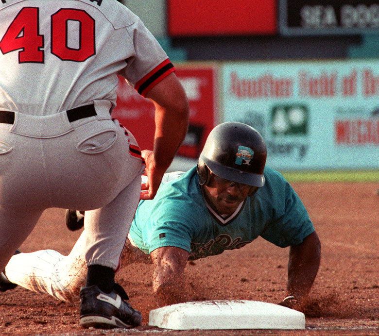 STAFF PHOTO BY JOHN PATRIQUIN -- Friday, August 16, 1996 -- Sea Dogs #11 Quinn Mack dives back to first safely to first against Harrisburg #40 Scott Talanoa during action at Hadlock Field. John Patriquin