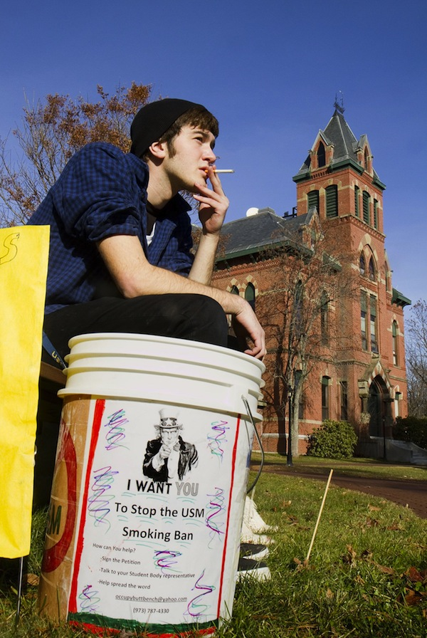 In this file photo, USM freshman Joshua Thornberg smokes during a protest of a proposed smoking ban on USM campuses at the Gorham campus on Monday December 3, 2012. Gov. LePage has vetoed a bill to ban smoking at all public Maine college campuses.
