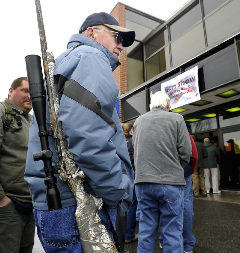 In this January 19, 2013 file photo, Sid Strom from Norway, ME waits for the opening for the Augusta Gun Show at the Augusta Civic Center. The Maine Senate voted 19-16 on Thursday, May 30, 2013 to defeat a bill that would require background checks for all firearms sales at gun shows, a major loophole that allows violent offenders to easily get their hands on weapons, gun-control advocates say.