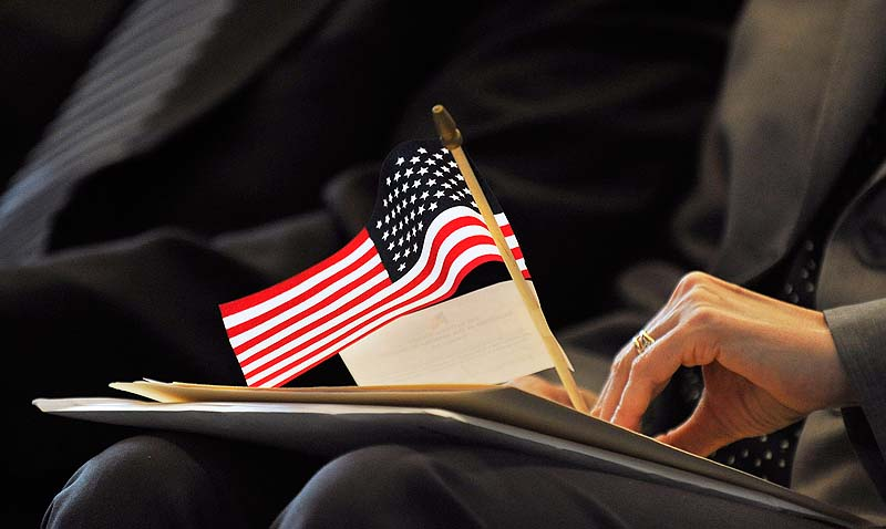 A new citizen holds a small American flag during a naturalization ceremony at Portland High School on Friday.