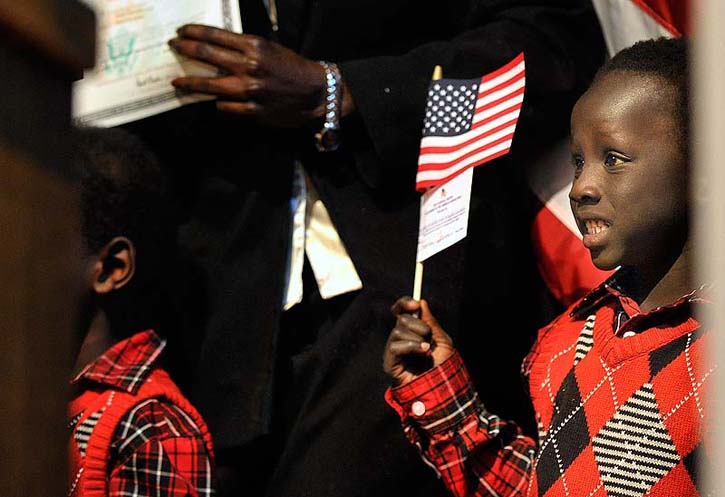 Kandok Ring smiles for a family photo after his mother, Nybol Lual, originally of Sudan, became a U.S. citizen at a naturalization ceremony on Friday at Portland High School.