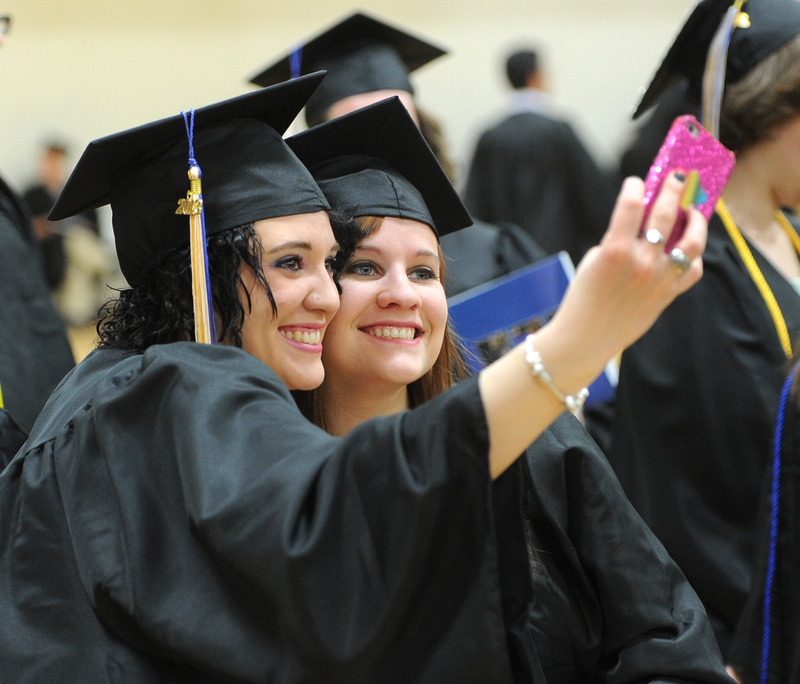Mariah Bosse of Scarborough and Kristen Stearns of Lyman take photos before the graduation ceremony Saturday at the University of Southern Maine in Gorham.