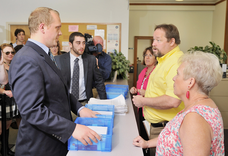 Tom MacMillan, lift, chair of the Portland Green Independent Committee, presents petitions to the Portland City Clerk's office staff. The petitions seek to make marijuana legal in Portland. With him is David Boyer, center, Maine political director for the Marijuana Policy Project. From right are Georgia Taylor, election assistant; Bud Philbrick, election administrator; and Katherine Jones, Portland city clerk.