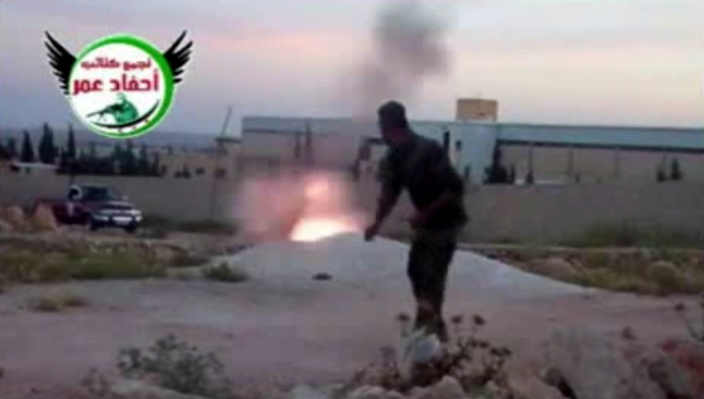 This image from amateur video, which is consistent with AP reporting, shows a rebel fighter firing a mortar with the help of a drawstring in Aleppo, Syria, on Tuesday.