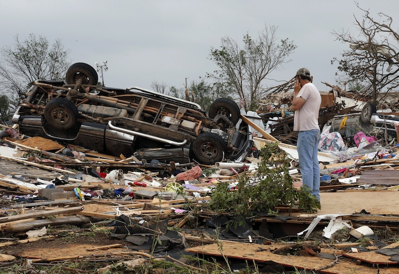 John Warner surveys the damage near a friend's mobile home in the Steelman Estates Mobile Home Park, destroyed in Sunday's tornado, near Shawnee, Okla., Monday, May 20, 2013. (AP Photo Sue Ogrocki)