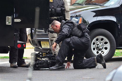 A state police SWAT team member readies a robot to enter a home where a man had barricaded himself on Friday in Trenton, N.J.