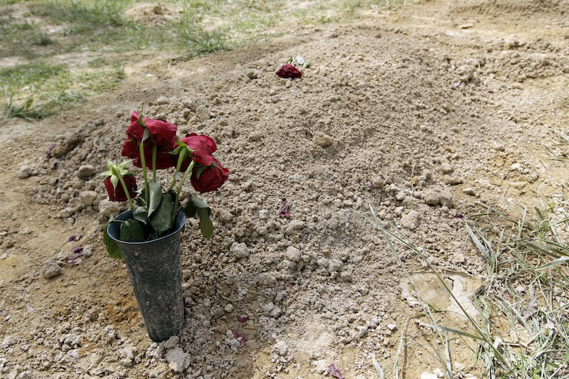Flowers are placed on the alleged burial site of Boston Marathon bombing suspect Tamerlan Tsarnaev in Doswell, Va., Friday, May 10, 2013. Tsarnaev's uncle Ruslan Tsarni said Tsarnaev was buried in the cemetery in Doswell, near RichmondVa. Tsarnaev was killed April 19 in a getaway attempt after a gunbattle with police. His younger brother, Dzhokhar, was captured later and remains in custody. (AP Photo/Luis M. Alvarez)