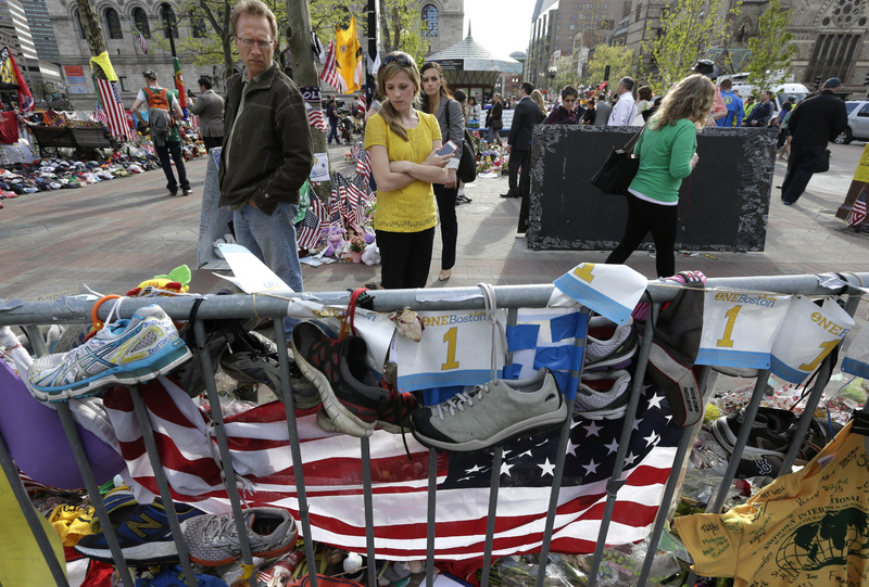 People pause Tuesday to look at a makeshift memorial for those killed and injured in the Boston Marathon bombings near the finish line in Boston's Copley Square.