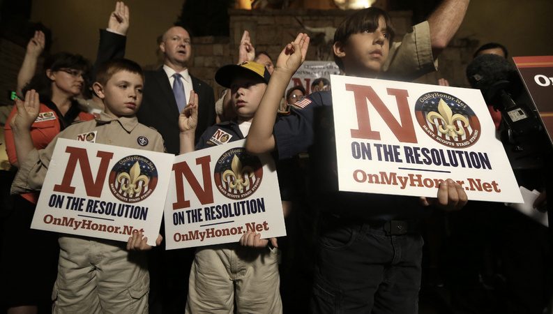 Boy Scouts from right, Joey Kalich, 10, Steven Grime, 7, and Jonathon Grime, 9, raise their hands at the close of a news conference held by people against the change in the Boy Scouts of America policy on gay scouts Wednesday in Grapevine, Texas.