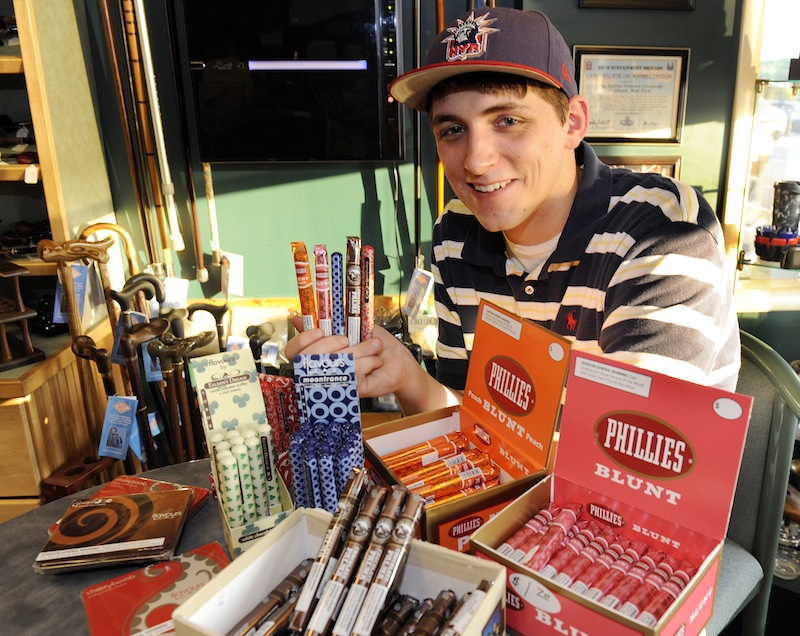 Cigar enthusiast Brendan Glennon poses with a display of candy-flavored cigars at a custom tobacco shop in Albany, N.Y., Friday, May 31, 2013. The American Cancer Society is pushing to make New York the first state to enact a comprehensive restriction on the sale of candy-and fruit-flavored cigarillos, chewing tobacco and tobacco used in water pipes. (AP Photo/Hans Pennink)