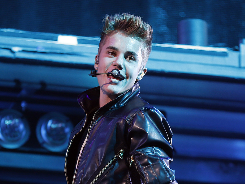 Justin Bieber, shown performing at the MGM Grand Garden Arena in Las Vegas, was able to dodge a fan who rushed the stage and was tackled by security officers in Dubai. Head and Shoulders,Looking Over Shoulder,Microphone,One Person,Popped Collar,Spiked Hair,Upturned Collar