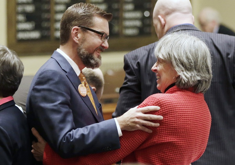 In this May 9, 2013 file photo, gay marriage sponsors Rep. Karen Clark, right, and Sen. Scott Dibble celebrate after the Minnesota House passed the gay marriage bill in St. Paul, Minn. The two openly gay Minnesota state lawmakers, who respectively sponsored the measure in the state House and Senate, prepared to watch Democratic Gov. Mark Dayton sign the bill in a ceremony Tuesday, May 14, 2013, on the front steps of Minnesota's Capitol. (AP Photo/Jim Mone, File)