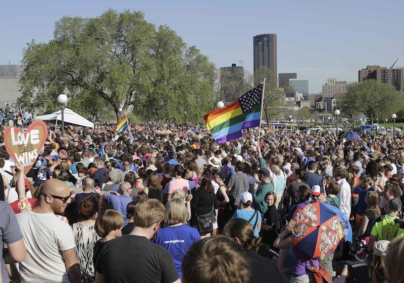 An estimated 6,000 people gathered at the State Capitol where Minnesota Gov. Mark Dayton signed the gay marriage bill, Tuesday, May 14, 2013, in St. Paul, Minn. Minnesota becomes the 12th state to legalize gay marriage. (AP Photo/Jim Mone)