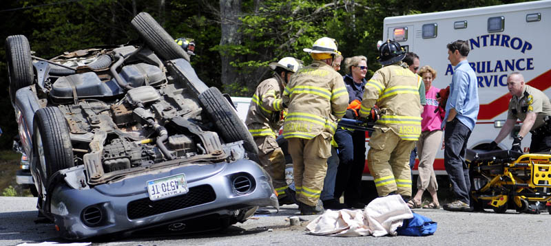Rescue workers carry a 17-year-old Leeds driver to an ambulance Sunday, after the sport utility vehicle she was driving rolled over in Wayne.