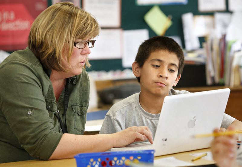 Sixth-grade teacher Lisa Hatch works with Emmanuel Iglesias Tuesday, May 27, 2013, on a laptop during class at King Middle School. The class uses laptops that are seven or eight years old.