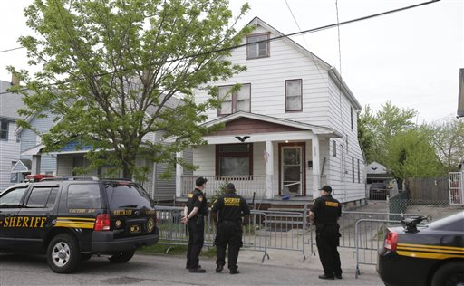 Sheriff deputies stand outside the house on Seymour Avenue in Cleveland where three women who vanished a decade ago were found.