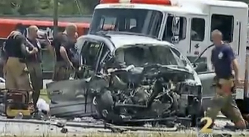 In this image taken from video, emergency personnel work the scene of a car crash Friday, May 31, 2013, in Jonesboro, Ga. Former NBA All-Star guard Daron