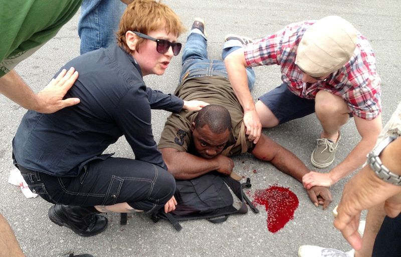 Bystanders comfort a shooting victim while awaiting medical assistance at Frenchmen and N. Villere streets in New Orleans.