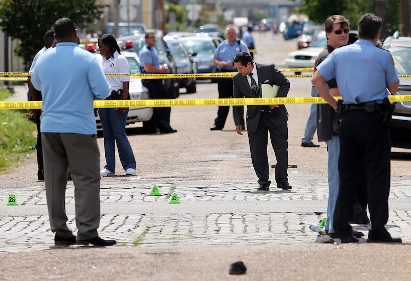 New Orleans police officers investigate the scene at the intersection of Frenchmen and N. Villere Streets in New Orleans after gunfire at a Mother's Day second-line parade on Sunday, May 12, 2013. Police spokeswoman Remi Braden said in an email that many of the 17 victims were grazed and most of the wounds weren't life-threatening. No deaths were reported. (AP Photo/The Times-Picayune, Michael DeMocker)