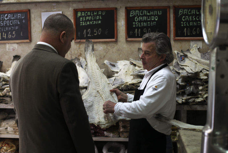 Jose Martins, right, shows a piece of dried cod to a customer in the food store where he works in downtown Lisbon on Thursday.