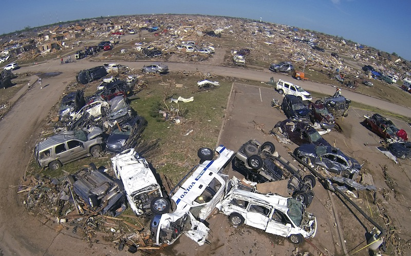 A pile of destroyed cars of teachers sits outside Briarwood elementary school in Oklahoma City, Oklahoma May 22, 2013. Rescue workers with sniffer dogs picked through the ruins on Wednesday to ensure no survivors remained buried after a deadly tornado left thousands homeless and trying to salvage what was left of their belongings. Curvature of horizon in the photo is due to an ultra-wide angle lens. (REUTERS/Rick Wilking) :rel:d:bm:GF2E95M1QVR01