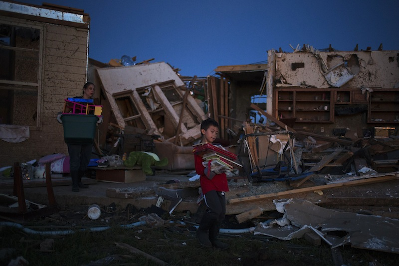 Ethan, 7, carries books he recovered from his damaged house in Moore, Oklahoma, two days after the Oklahoma City suburb was left devastated by a tornado on May 22, 2013. Tornado survivors thanked God, sturdy closets and luck in explaining how they lived through the colossal twister that devastated an Oklahoma town and killed 24 people, an astonishingly low toll given the extent of destruction. (REUTERS/Adrees Latif) :rel:d:bm:GF2E95N05Z501