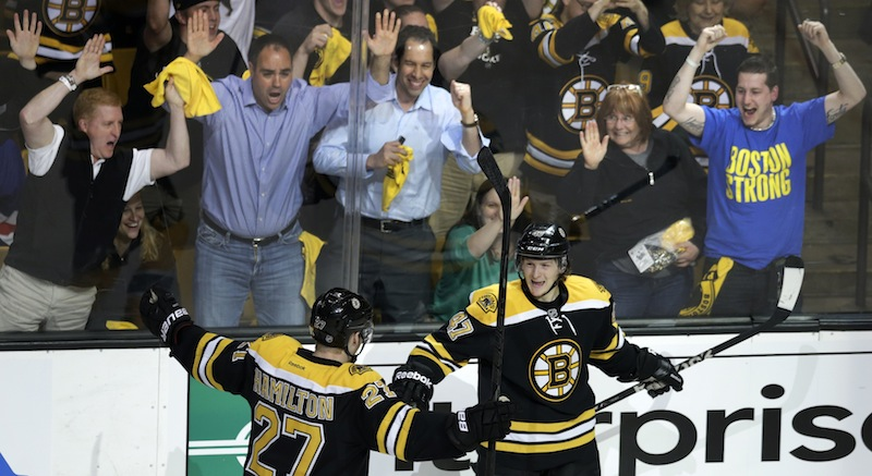 Fans celebrate as Boston Bruins defenseman Torey Krug, front right, is congratulated by teammate Dougie Hamilton after his goal against the New York Rangers during the third period in Game 1 of an NHL playoff series Thursday in Boston.