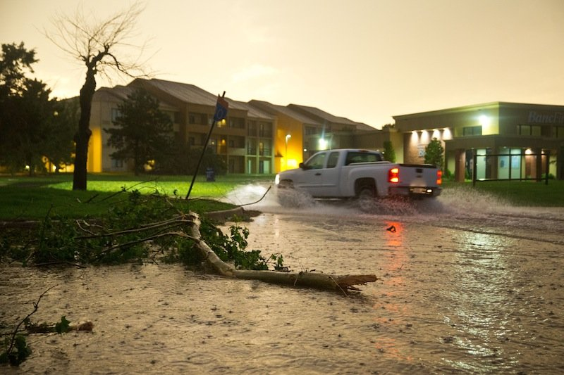 A pickup truck drives through a flooded Highline Blvd just east of South Meridian Ave where several trees were also down after a tornado on the ground near El Reno Okla. just south of Interstate 40 on Friday May 31, 2013. (AP Photo/The World-Herald, Chris Machian)