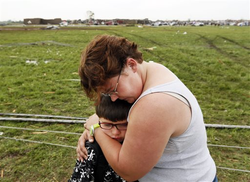 Rebekah Stuck hugs her son, Aiden Stuck, 7, after she found him in front of the destroyed Briarwood Elementary after a tornado struck south Oklahoma City and Moore, Okla., on Monday. Aiden was inside the school when it was hit.