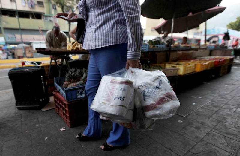 A woman who just bought toilet paper at a grocery store reads her receipt as she leaves the private store in Caracas, Venezuela, Wednesday, May 15, 2013. First milk, butter, coffee and cornmeal ran short. Now Venezuela is running out of the most basic of necessities _ toilet paper. Economists say Venezuela's shortages stem from price controls meant to make basic goods available to the poorest parts of society and the government's controls on foreign currency. (AP Photo/Fernando Llano)