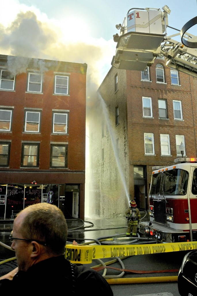 Main Street in Waterville is closed as firefighters work in an alley to extinguish fires in the facing building Friday afternoon.