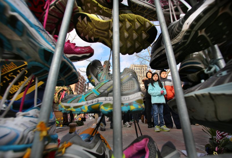 Visitors pause in Boston's Copley Square last week to view a growing collection of running shoes that are part of a makeshift memorial for the victims of the Boston Marathon bombings. The Portland Symphony Orchestra will perform Mahler's Fifth Symphony in memoriam on Sunday and Tuesday.