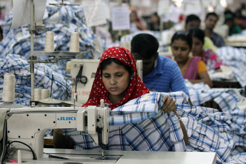 "A woman works at a garment factory in Ashulia, Bangladesh. Very few companies sell clothing that's made in factories that maintain safe working conditions. In fact, ""ethically made"" clothes make up a tiny fraction of 1 percent of the $1 trillion global fashion industry."