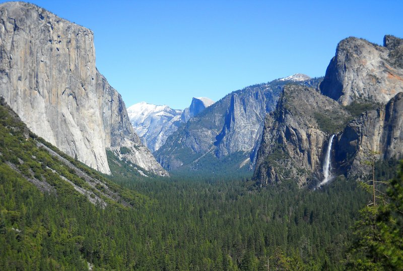 Yosemite Valley as seen from Tunnel View with three of the park's best-known natural attractions: El Capitan summit on the left, the granite peak known as Half Dome in the distant center and Bridalveil Fall on the right.