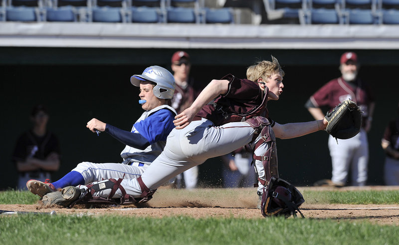 Sean McDermott of Old Orchard Beach slides across the plate in the first inning Wednesday as Freeport catcher Brian Rhea awaits the throw. Rhea hit a two-run single in the seventh inning as Freeport rallied to a 7-4 victory at The Ballpark.