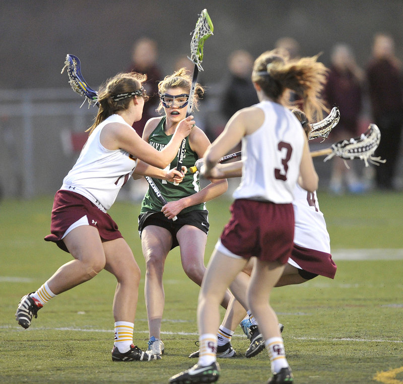 Walker Foehl of Waynflete finds herself surrounded by Cape Elizabeth defenders while trying to head to goal Wednesday night. Waynflete won in girls' lacrosse, 10-8.