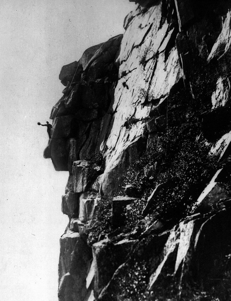 In this 1916 photo provided by the Littleton Area Historical Society, Edward Geddes waves his hat a he stands on the chin of the Old Man of the Mountain in Franconia, N.H. Geddes, a stone quarry superintendent from Quincy, Mass., was the first man to do repair work on New Hampshire's iconic figure, which fell nearly ten years ago. (AP Photo/Littleton Area Historical Society, Rev. Guy Roberts)